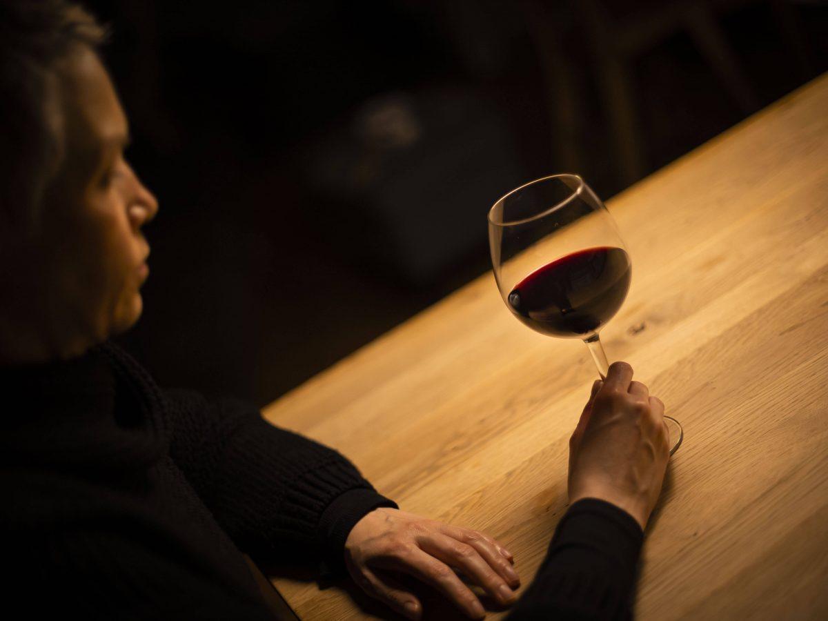 Person mit einem Glas Rotwein.