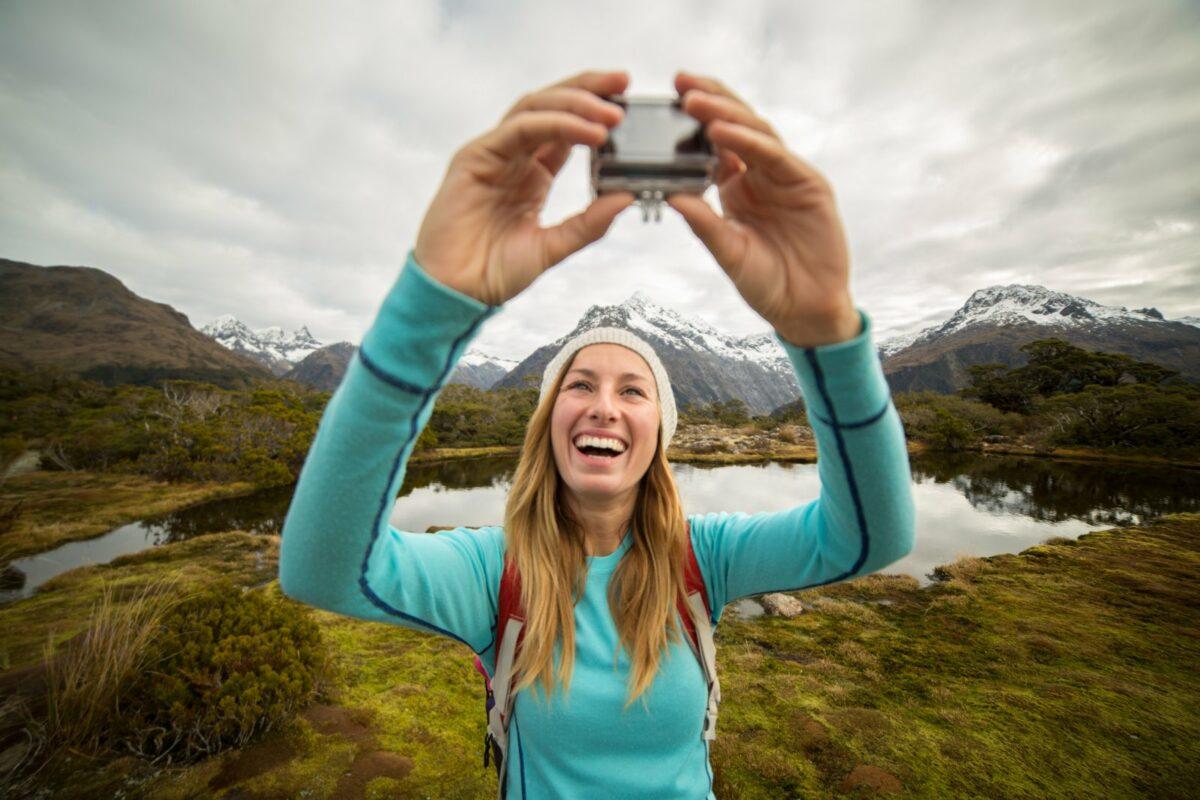 Frau macht in den Bergen ein Selfie mit einer Action-Cam.
