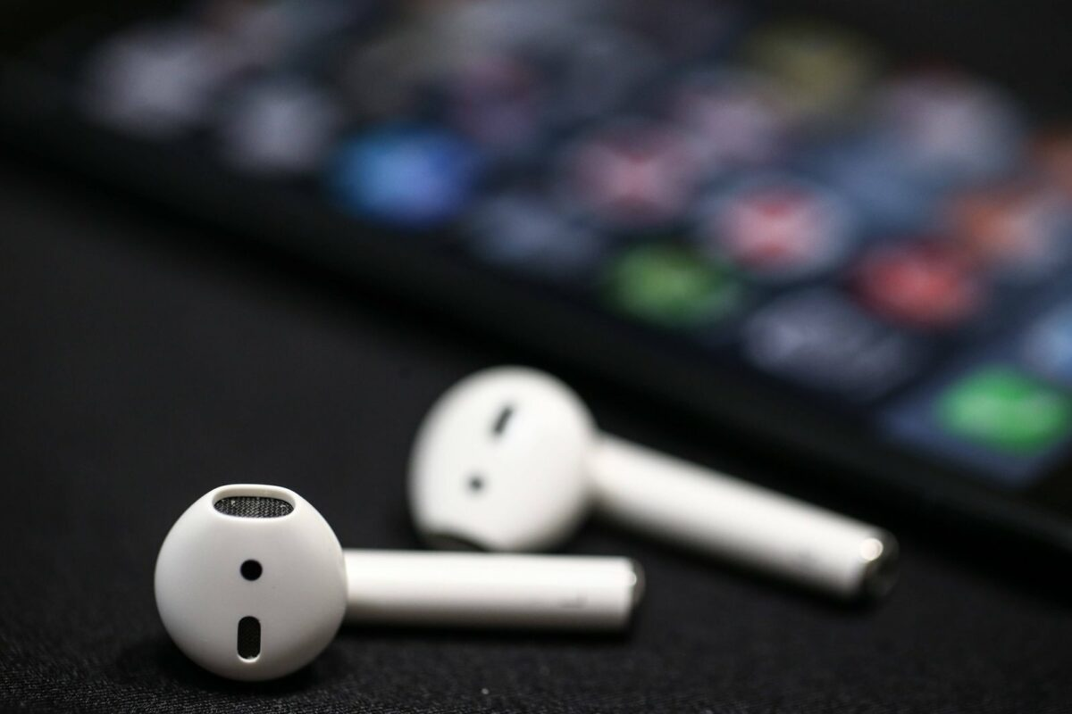 Apple AirPods liegen vor einem iPhone