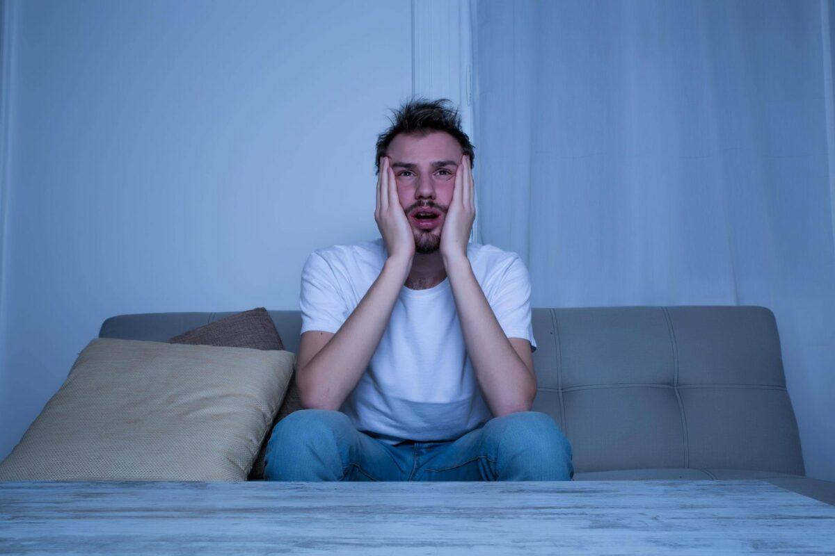 Mann sitzt auf dem Bett und guckt schockiert.