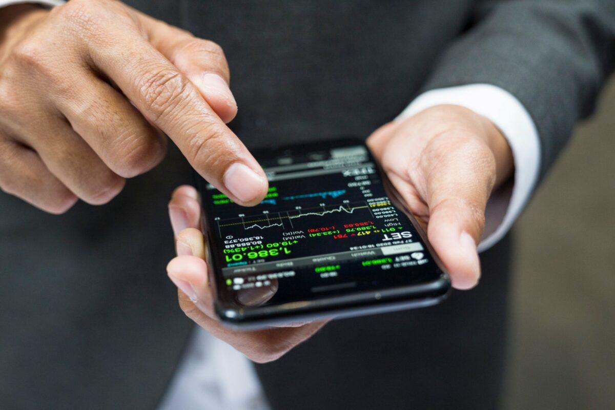 Mann mit Handy und Aktien-App.
