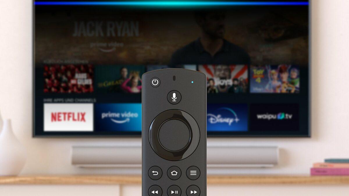 Ein Amazon Fire TV Stick im Vordergrund. Dahinter ein Fernseher mit der Amazon Fire TV-App.