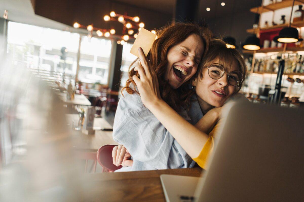Zwei Frauen umarmen sich freudig vor einem Laptop.