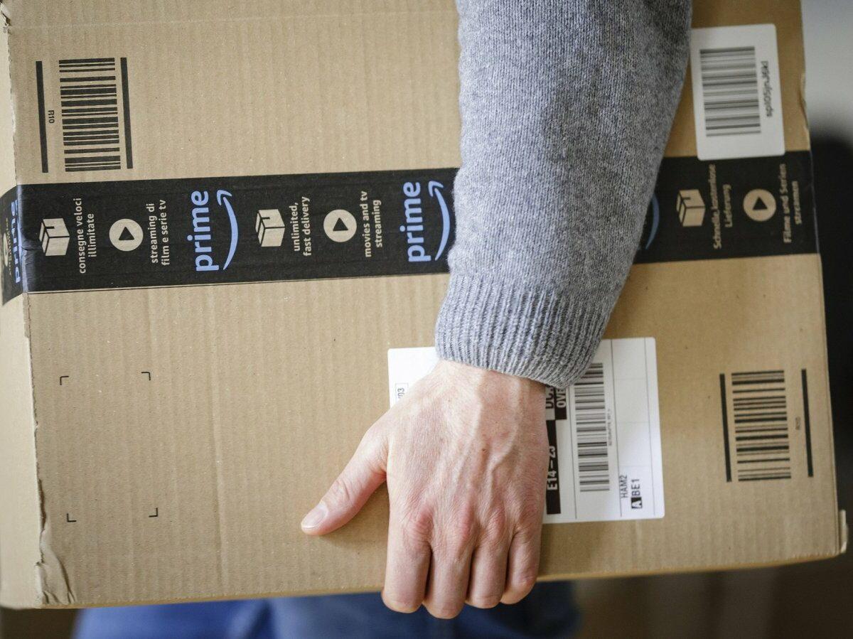 Mann mit Amazon Prime Paket in der Hand.