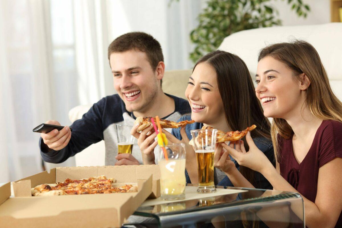 Drei Freunde essen Pizza und schauen fern.