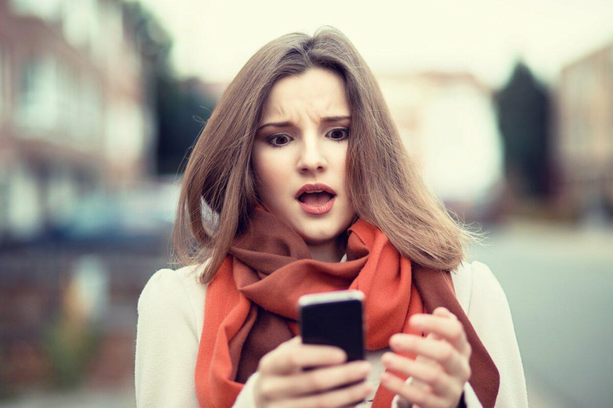 Frau guckt schockiert auf ihr Handy.