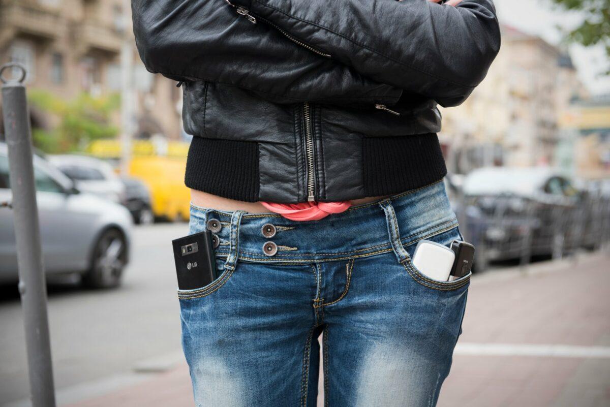 Frau mit Handys in den Hosentaschen