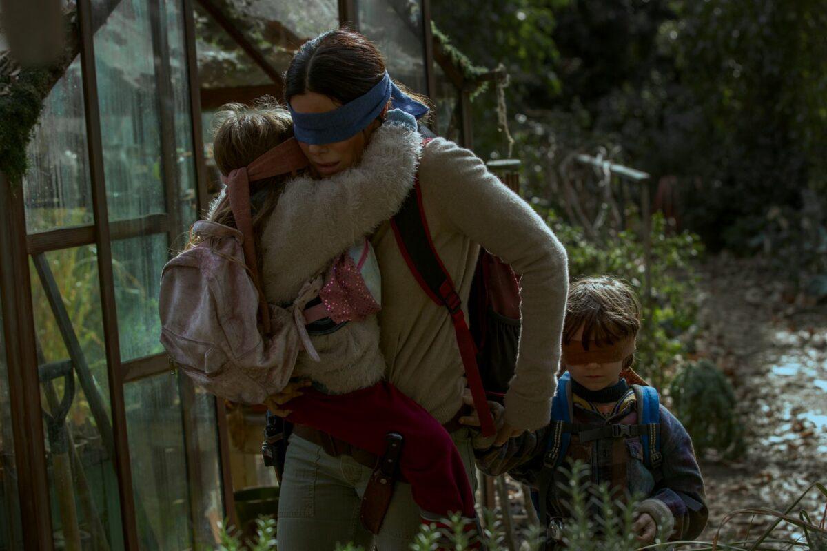 """Sandra Bullock läuft mit ihren Kindern durch den Wald in einer Szene aus """"Bird Box""""."""