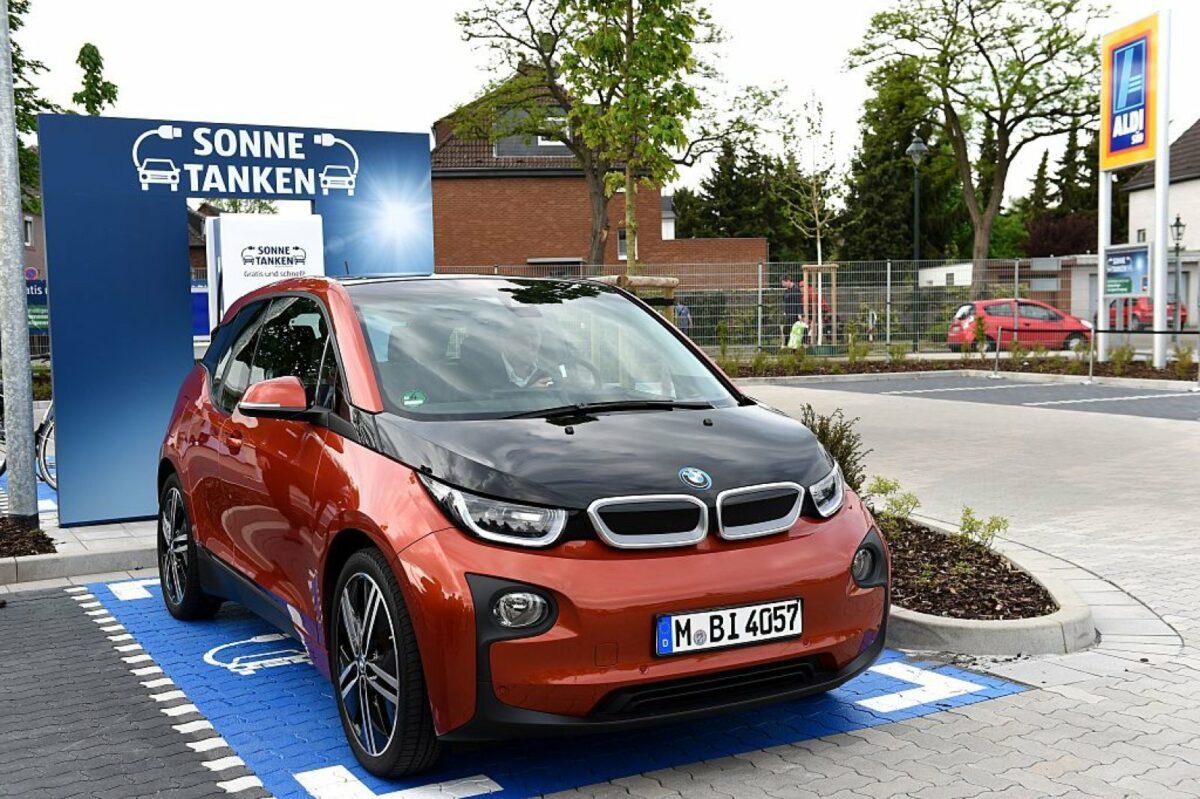 """Ein Elektroauto von BMW steht vor einer Werbewand mit der Aufschrift """"Sonne tanken""""."""