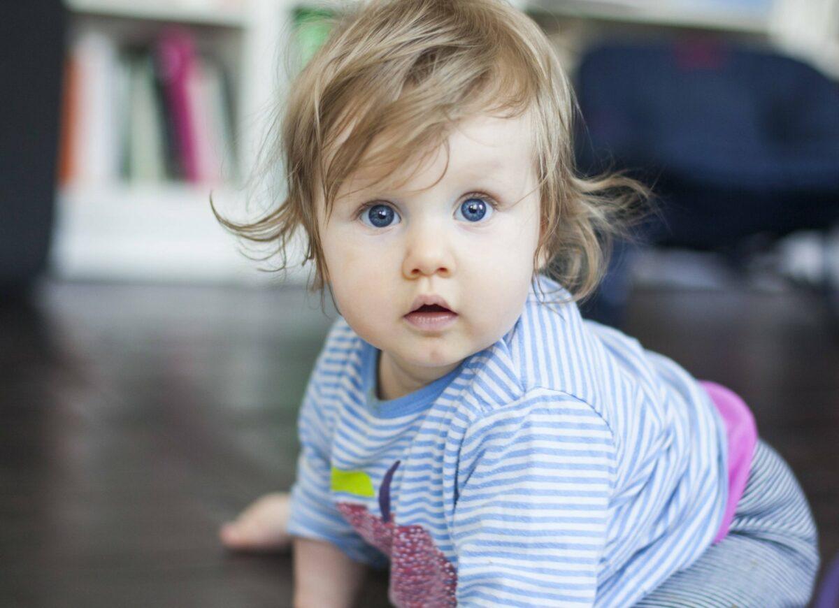 Ein Baby schaut erschrocken in die Kamera.