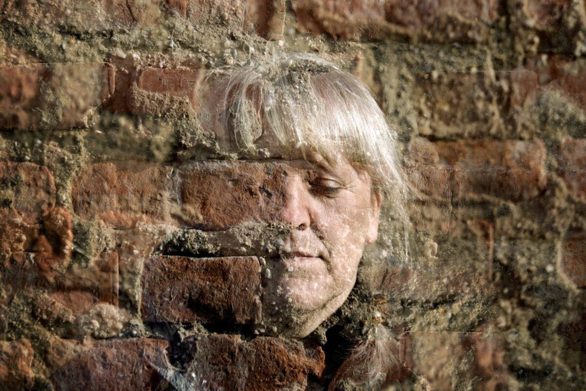 Eine Frau halb unsichtbar vor einer Backsteinmauer