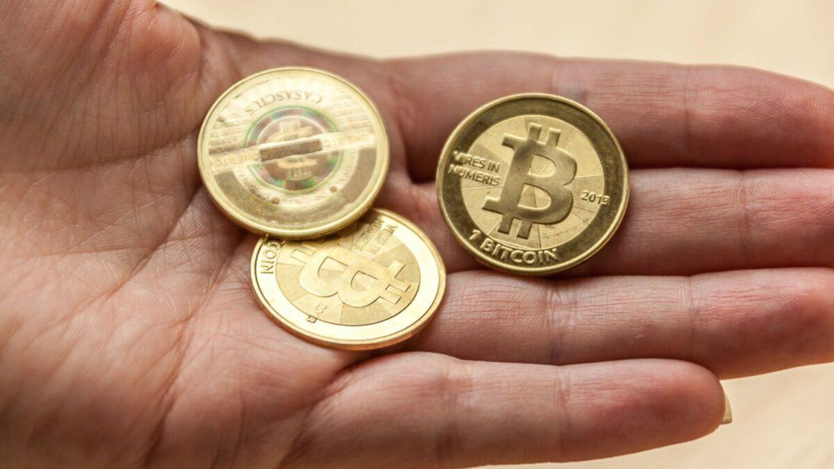 Eine Hand mit drei Bitcoin-Münzen