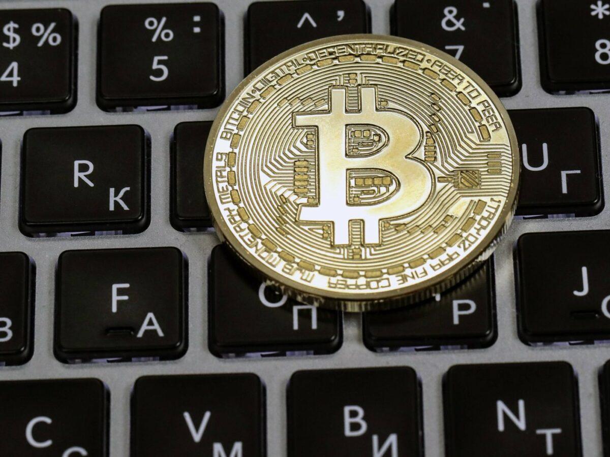 Ein Bitcoin liegt auf einer Tastatur.