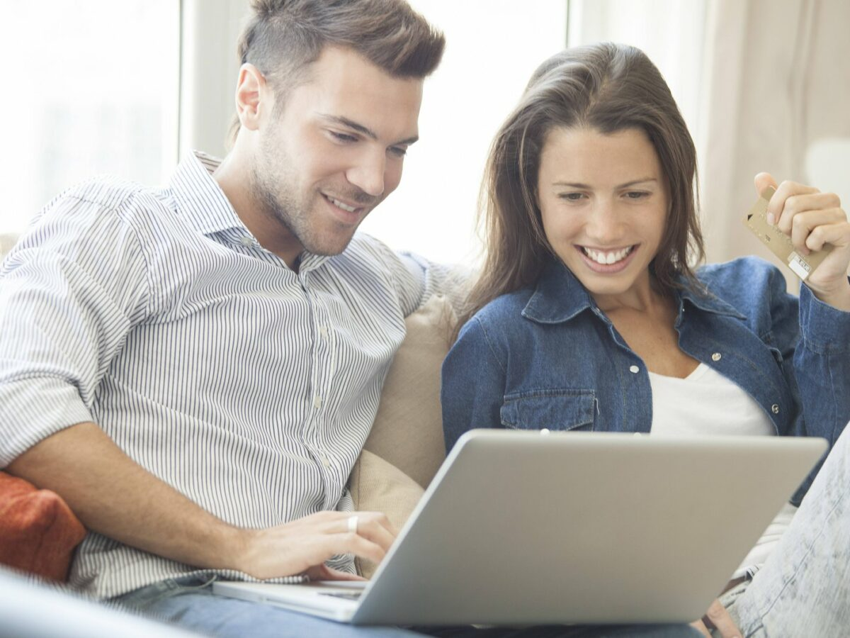 Pärchen sitzt lächelnd vor einem Laptop.