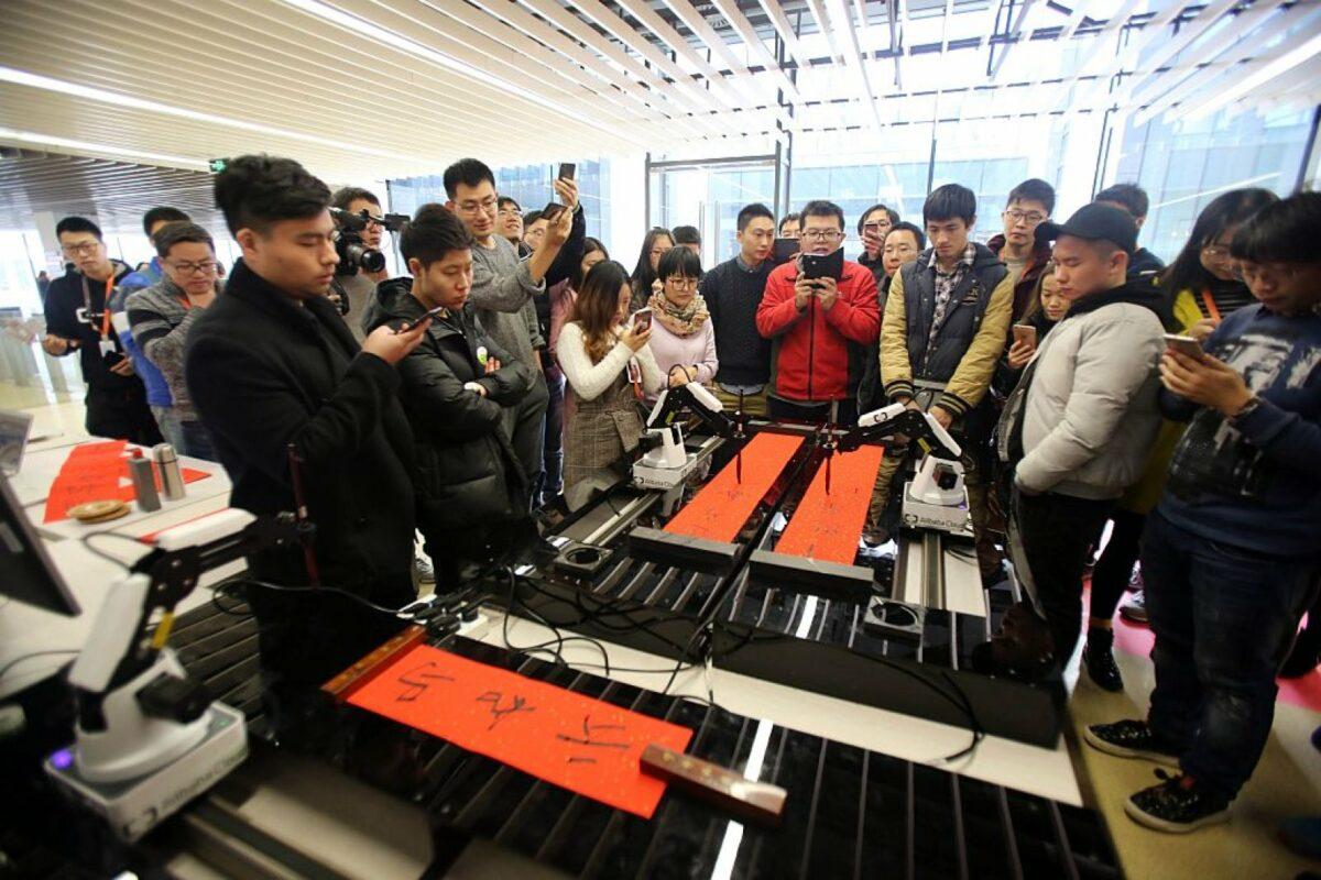 Alibaba-Mitarbeiter beobachten einen schreibenden Roboter