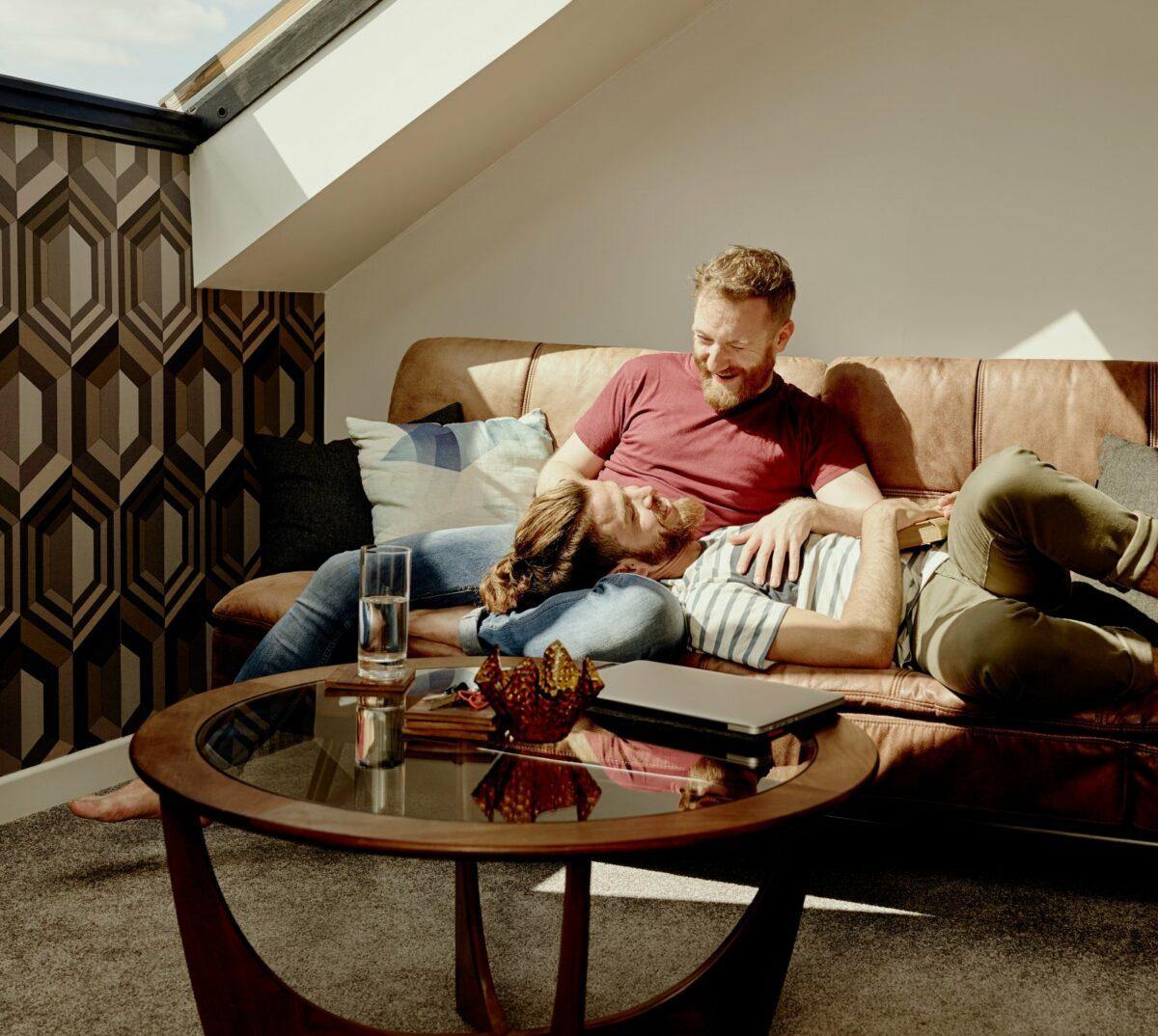 Zwei Männer sitzen in einem Luxusapartment auf dem Sofa.
