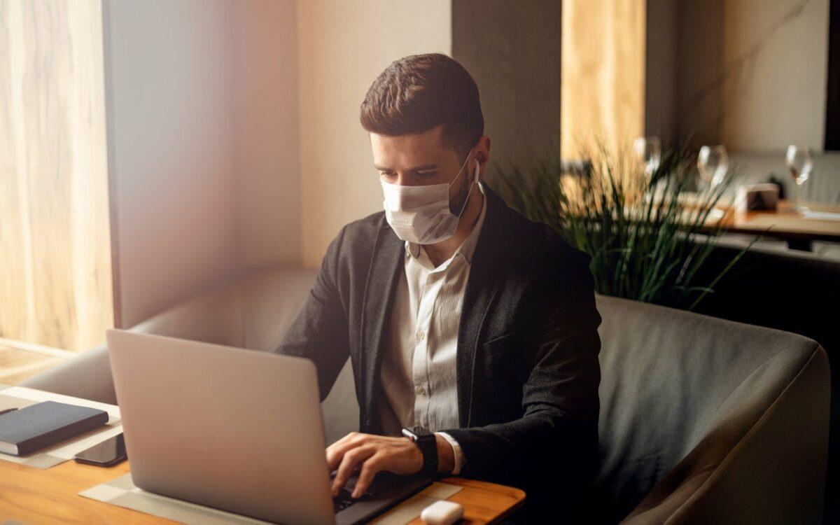 Mann sitzt mit Mundschutz vor einem Laptop.