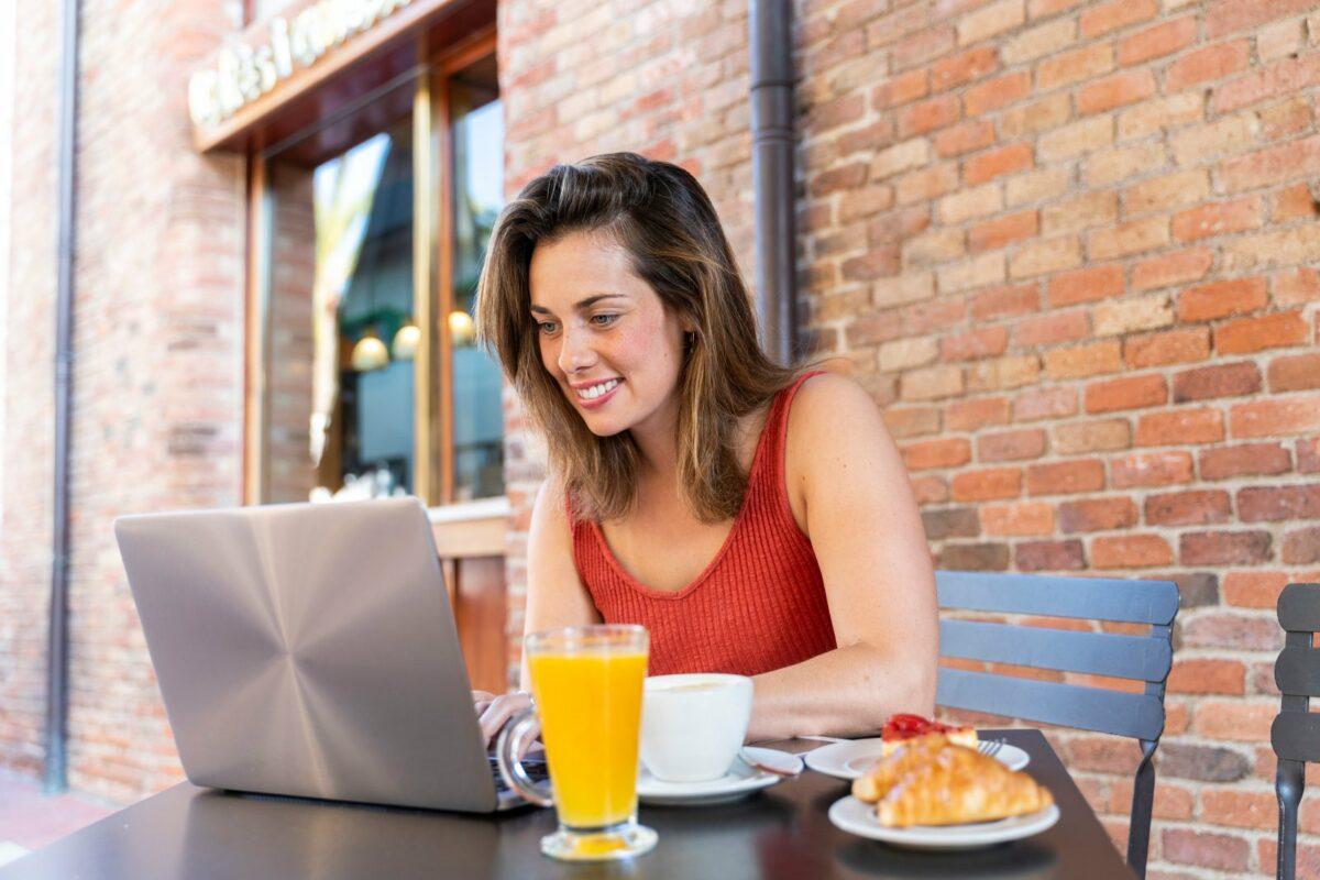 Frau sitzt lächelnd vor einem Laptop.
