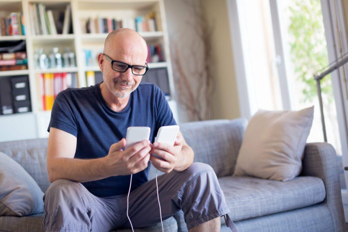 Mann überträgt Daten von seinem alten Handy auf das neue Gerät.