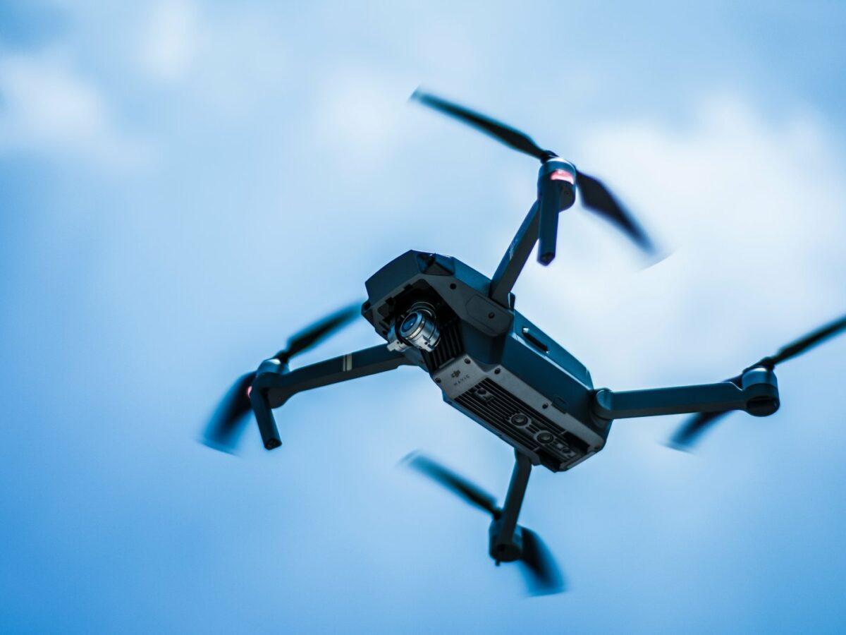 Eine Drohne fliegt vor blauem Himmel.