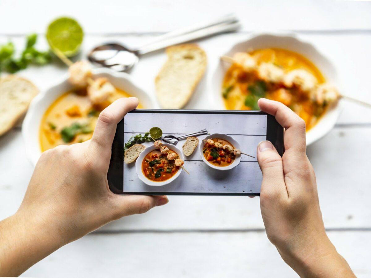 Junge Frau nimmt Foto ihres Essens auf