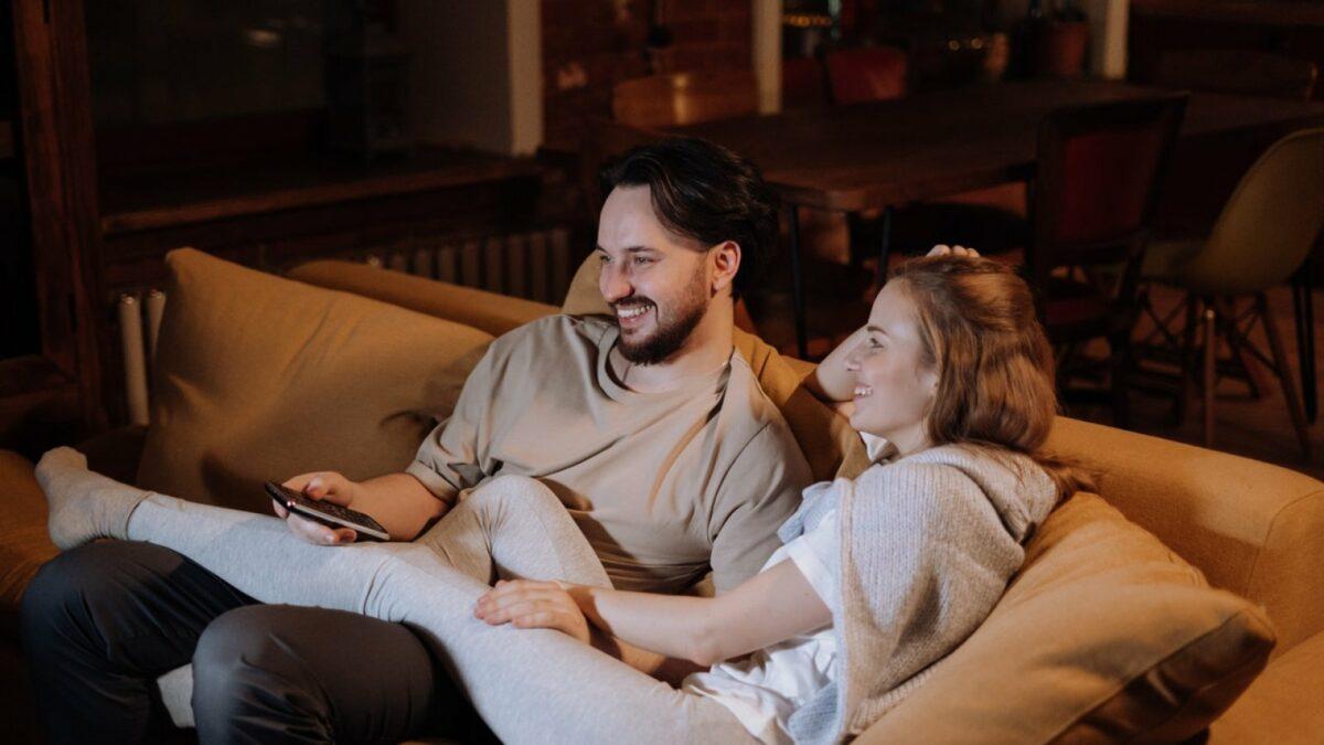 Eine Frau und ein Mann sitzen auf einem Sofa und schauen Fernsehen.