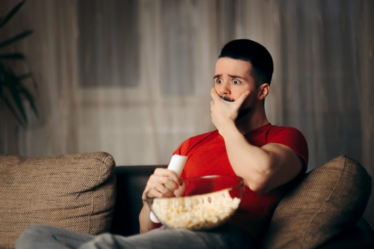 Man schaut einen Film und sitzt dabei auf dem Sofa. Er hat eine Schüssel Popcorn auf dem Schoß und ist erschrocken.