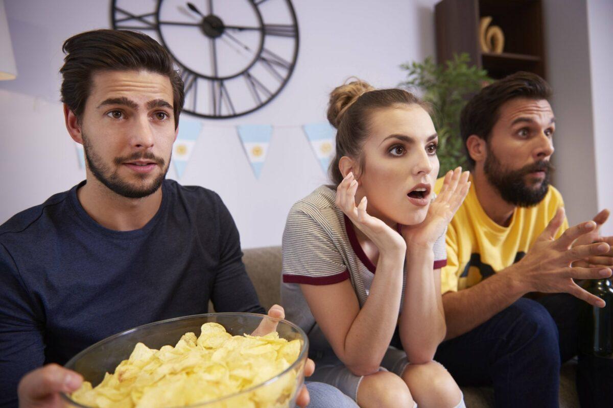 Überraschte Menschen vor dem Fernseher