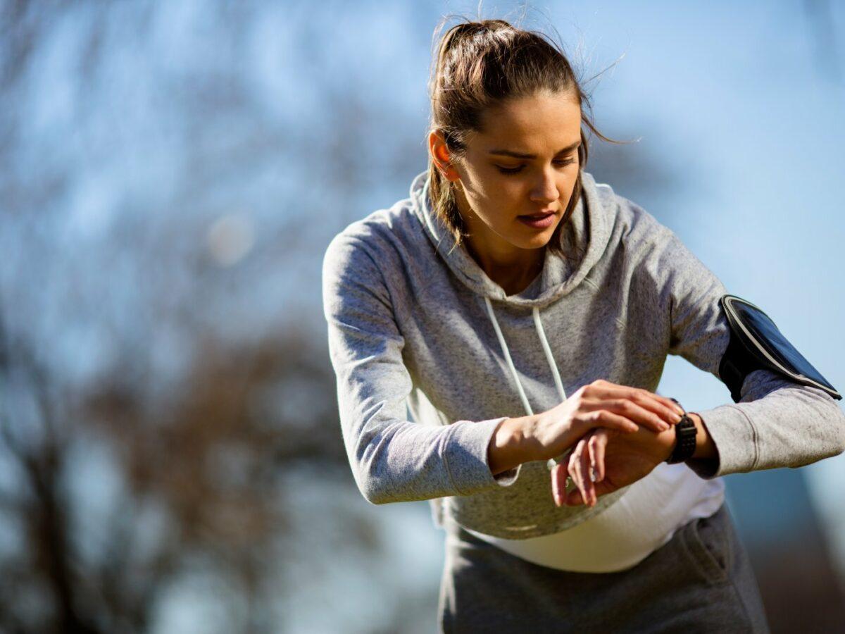 Junge Frau beim Joggen im Park guckt auf ihren Fitness-Tracker.