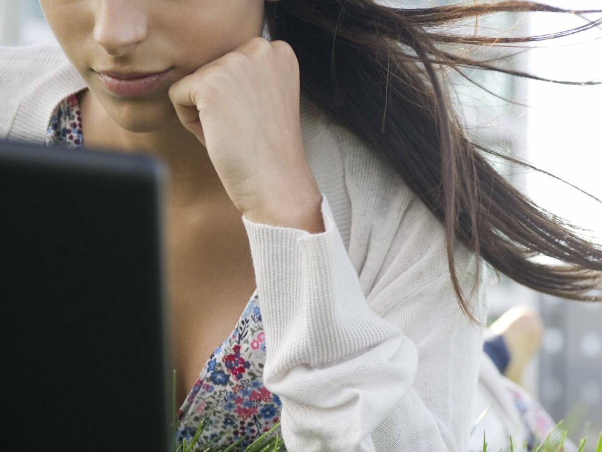 Eine Frau am Computer im Gras