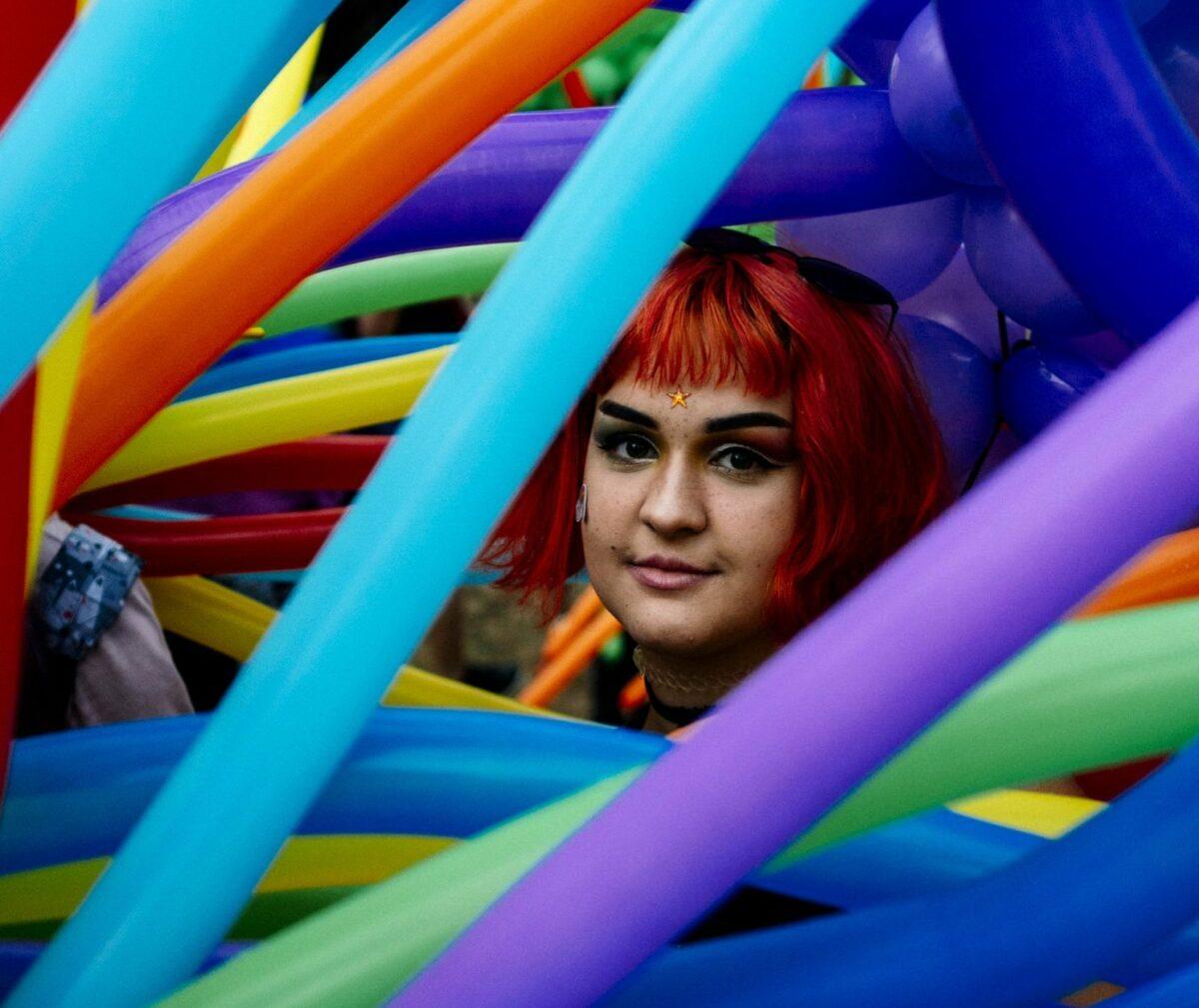 Frau mit roter Perücke in bunten Luftballons