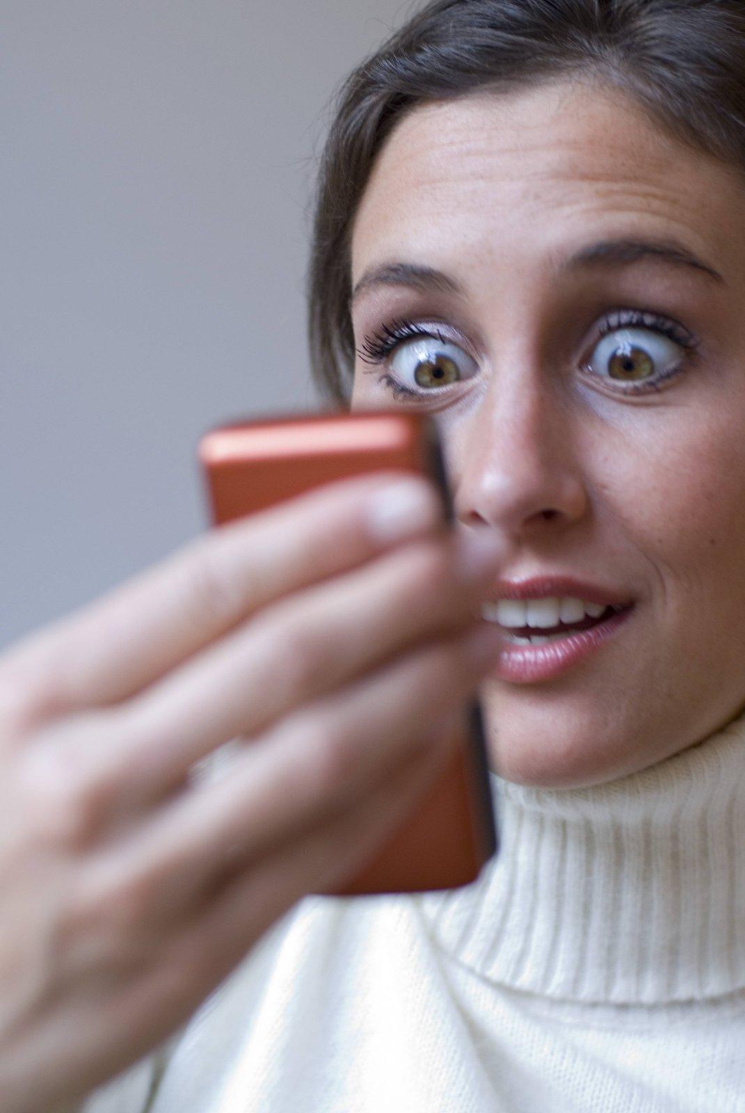 Frau schaut schockiert auf ihr Handy.