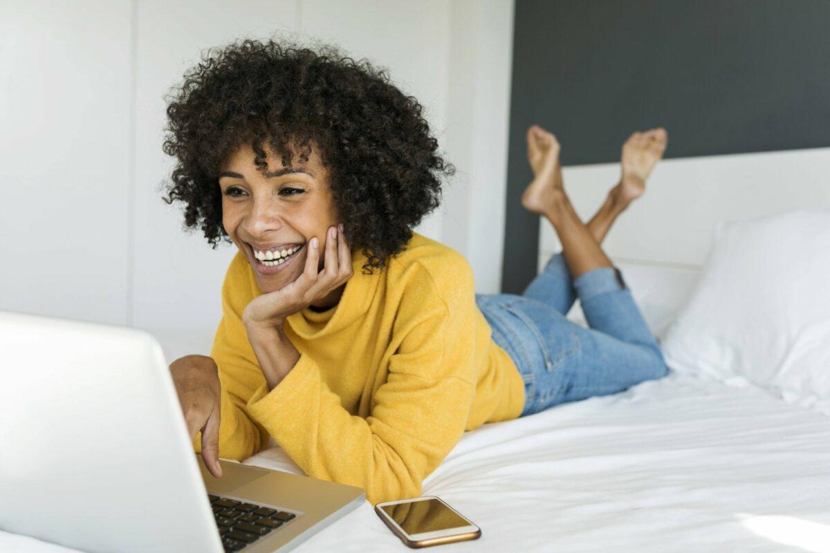 Frau auf dem bett schaut einen Filmauf demLaptop