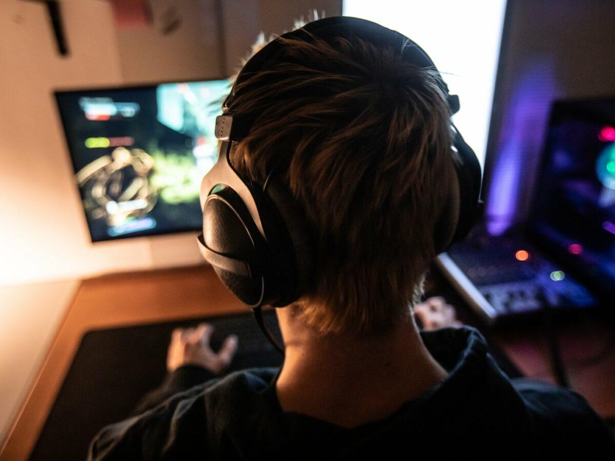 Junge mit Kopfhörer vor einem Bildschirm.