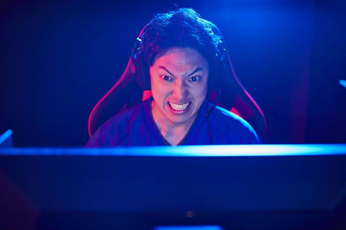 E-Sportler vor einem Gaming-Monitor