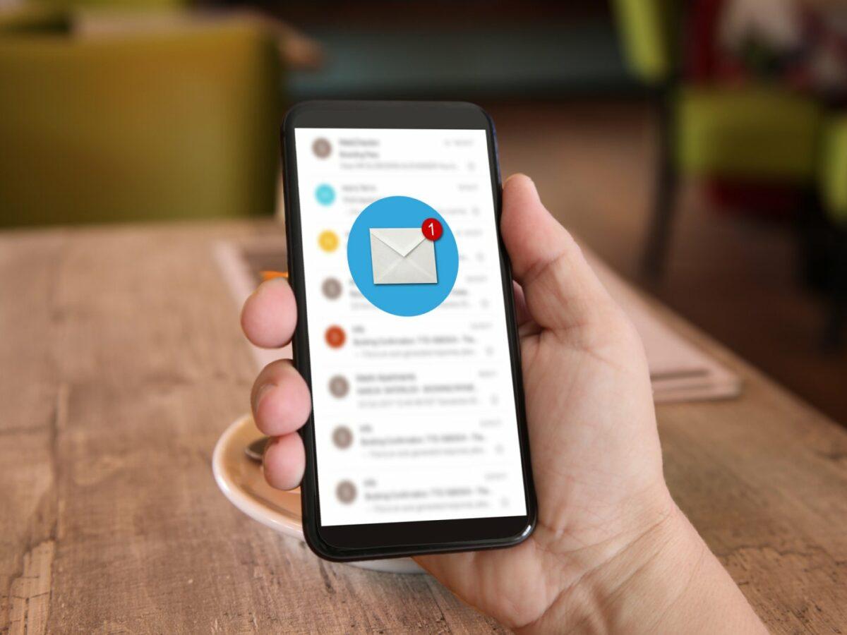 """Handy mit Symbol """"Neue Nachricht"""" in Hand über Tisch"""