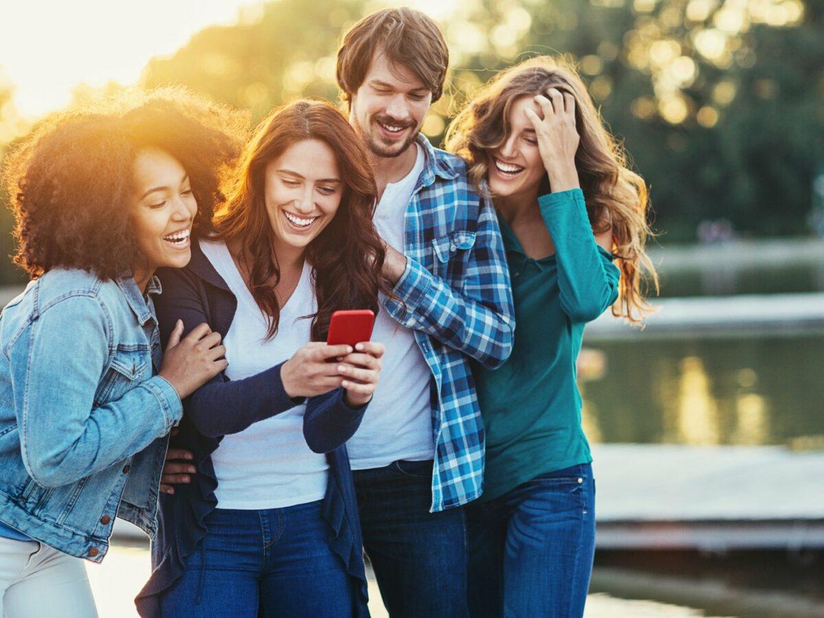 Eine Gruppe Menschen schaut lachend auf ein Smartphone.