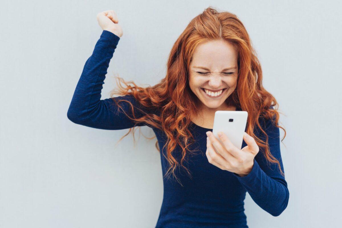 Frau mit Handy freut sich