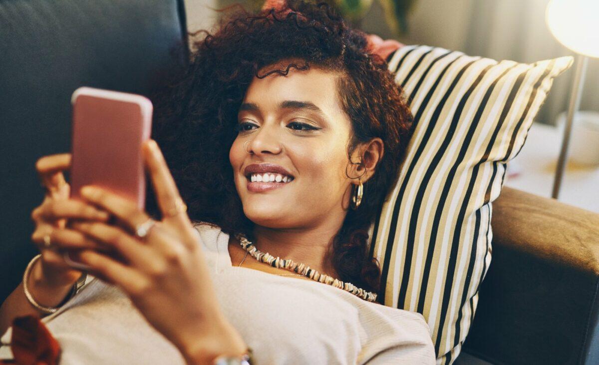 Frau schaut lächelnd auf ihr Handy.
