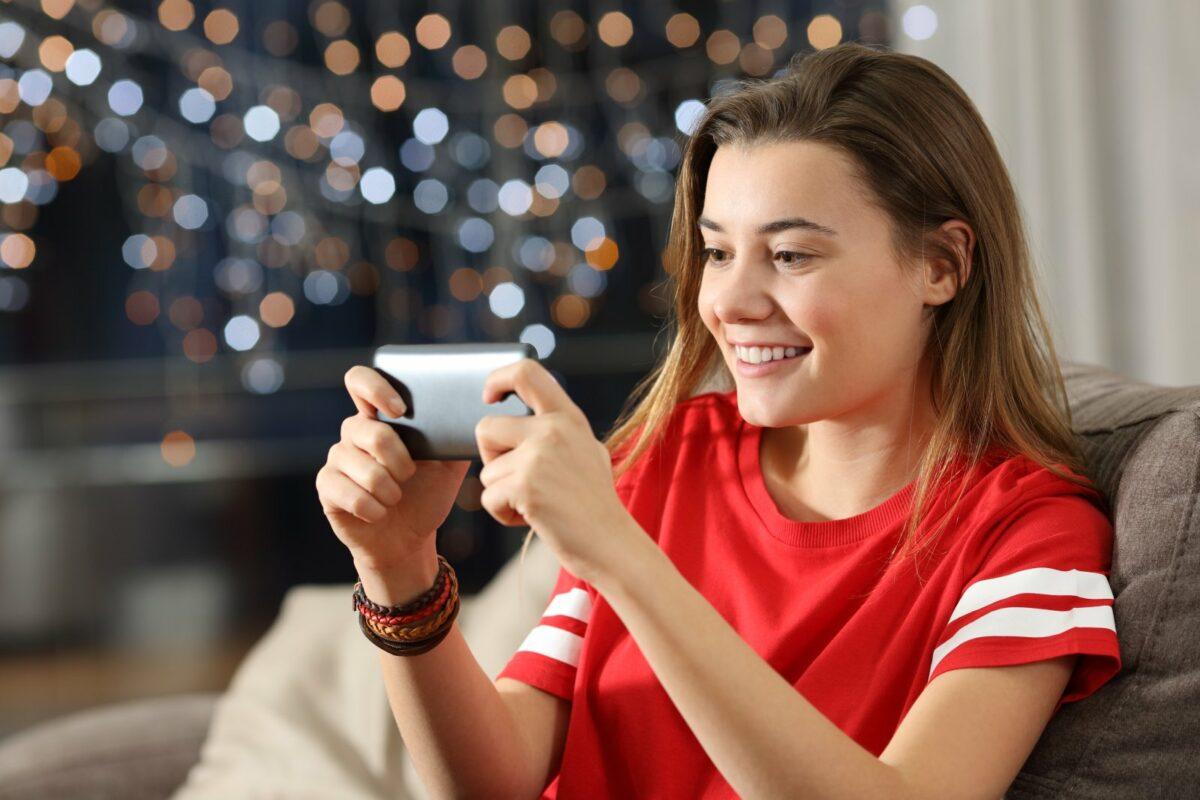 Frau spielt auf dem Smartphone.