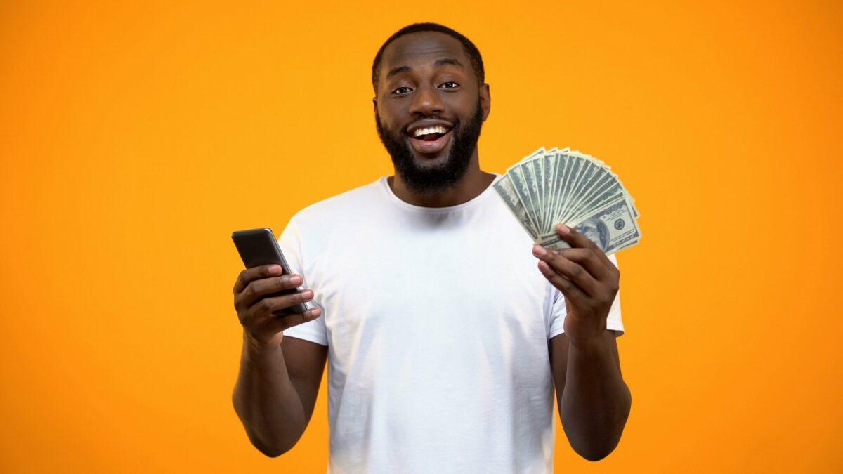 Mann mit Handy und Geld in der Hand.