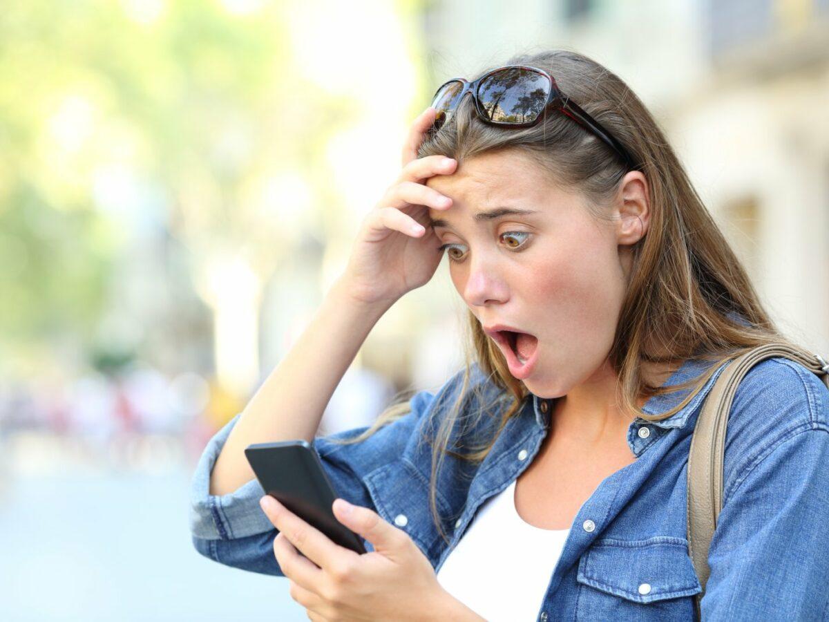 Frau guckt geschockt aufs Handy