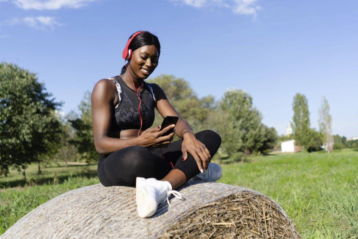 Frau in Sportoutfit mit Handy und Kopfhörern.