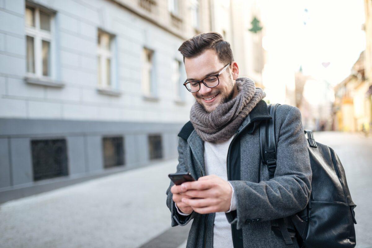 Mann guckt auf der Straße auf sein Handy.