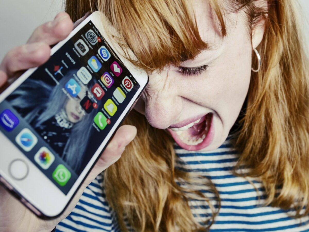 Frau wütend mit Handy.