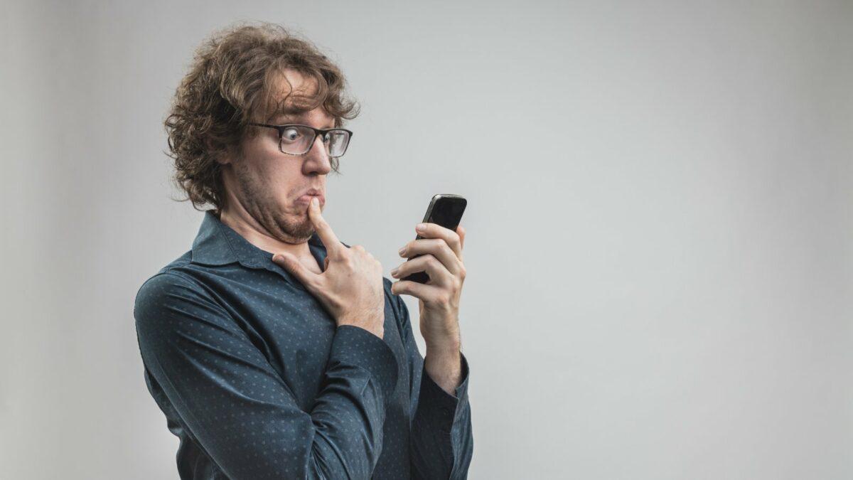 Mann guckt übertrieben fragend auf sein Handy