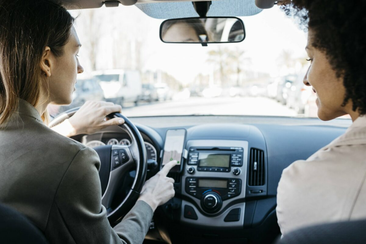 Frauen mir Smartphone im Auto