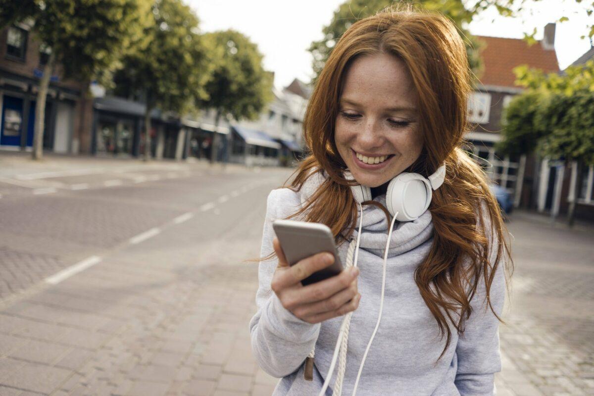 Eine Frau steht in der Stadt und schaut auf ihr Smartphone.