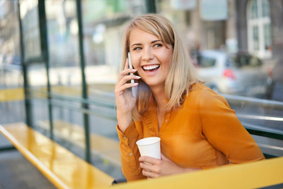 Frau telefoniert lachend mit ihrem Handy.