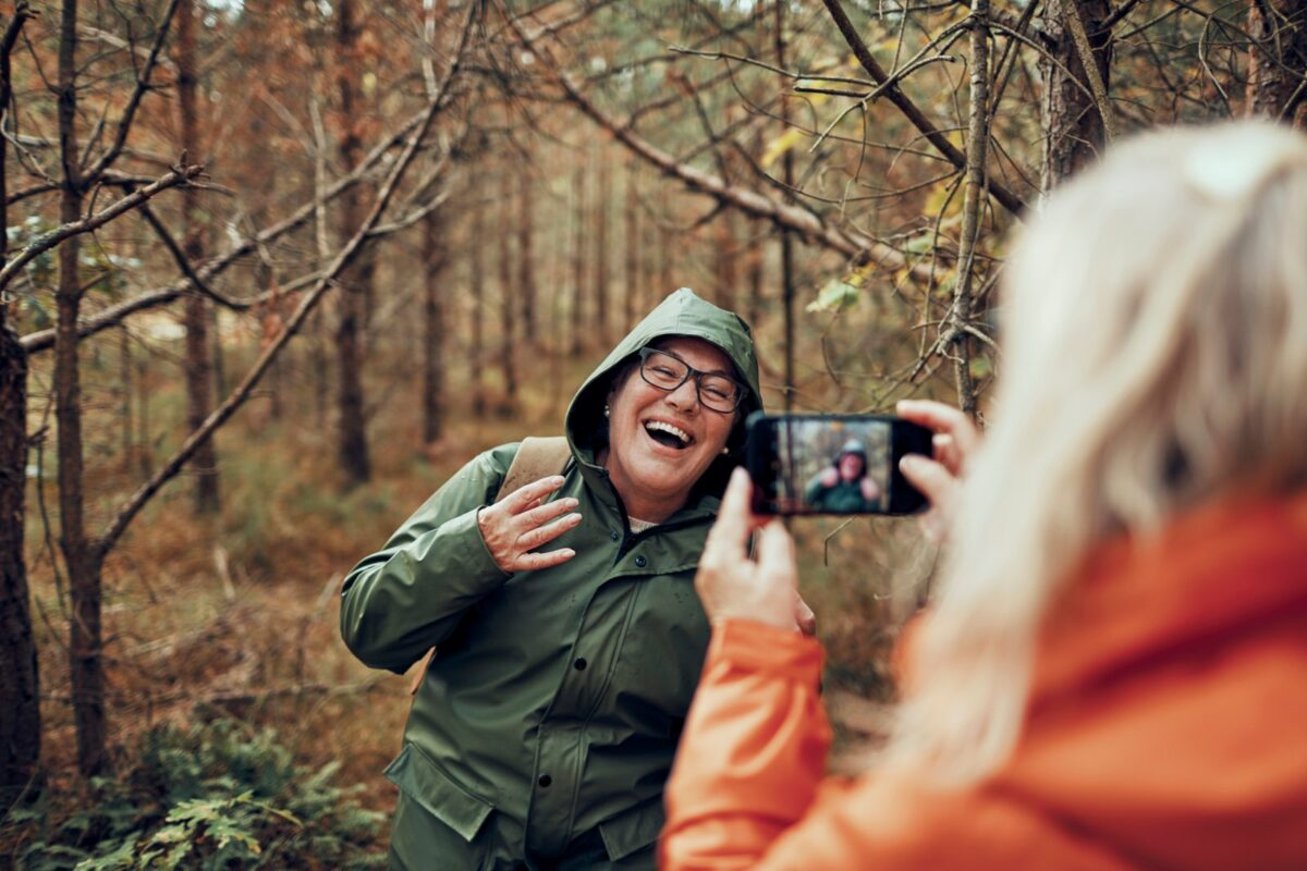 Frau nimmt Handyfoto in Herbstwald auf